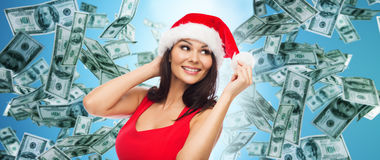Beautiful sexy woman in santa hat over money rain. People, holidays, christmas and finances concept - beautiful sexy woman in santa hat and red dress over dollar Royalty Free Stock Photo