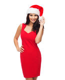 Beautiful sexy woman in santa hat and red dress. People, holidays, christmas and celebration concept - beautiful sexy woman in santa hat and red dress Royalty Free Stock Photography