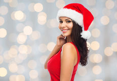 Beautiful sexy woman in santa hat and red dress. People, holidays, christmas and celebration concept - beautiful sexy woman in santa hat and red dress over Royalty Free Stock Photo