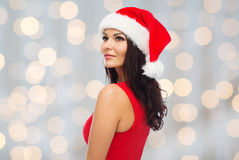 Beautiful sexy woman in santa hat and red dress. People, holidays, christmas and celebration concept - beautiful sexy woman in santa hat and red dress over Stock Image