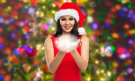 Beautiful sexy woman in santa hat and red dress. People, holidays, christmas and magic concept - beautiful sexy woman in santa hat and red dress showing fairy Stock Photo