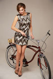 Beautiful sexy woman in short dress riding a bicycle Royalty Free Stock Image
