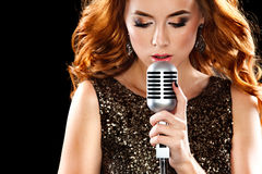 Beautiful sexy woman singing with the microphone. Beautiful Singing Girl. Beauty Woman with Microphone Royalty Free Stock Photos