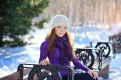 Beautiful and sexy woman sitting on bench in winter Royalty Free Stock Image