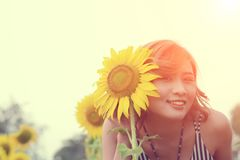 Beautiful woman with sunflower in sunflower fields smile at Stock Photography