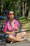 Beautiful sexy woman in sunglasses in the woods drinking water near bicycle Royalty Free Stock Image