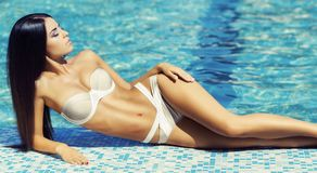 Beautiful and sexy woman in a swimwear relaxing near swimming pool. Traveling and vacation concept. Beautiful and sexy girl in a swimwear relaxing near swimming Stock Photos