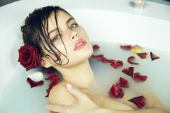 Beautiful sexy woman takes bath rose candles Valentine's day spa Stock Photos