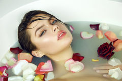 Beautiful sexy woman takes bath rose candles Valentine's day spa. Beautiful young sexy girl with dark hair wet, evening makeup, takes bath with milk and red pink Royalty Free Stock Photos