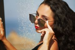 Beautiful woman taking a shower on the beach. Stock Images