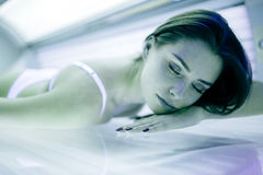 Beautiful woman tanning in solarium royalty free stock photo