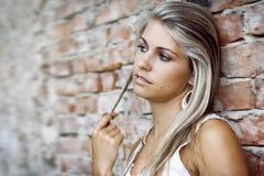 Beautiful sexy woman and wall of bricks - seductive look Royalty Free Stock Photos