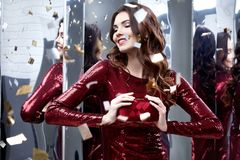 Beautiful sexy woman wear lux skinny shine red dress shiny sequi. Ns style for party celebrate New Year Christmas beauty salon hair style makeup perfect body Royalty Free Stock Image