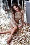 Beautiful sexy woman wear skinny gold dress shiny sequins style. For party celebrate New Year Christmas beauty salon long hair style makeup jewelry model pose Royalty Free Stock Photos