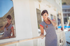 Beautiful woman wearing sailor striped dress posing at the sea Royalty Free Stock Photo