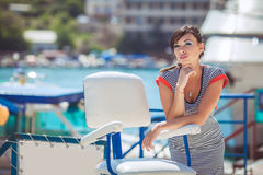 Beautiful sexy woman wearing sailor striped dress posing at the sea Stock Photography