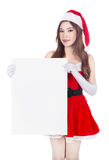 Beautiful sexy woman wearing santa claus clothes with blank sign Stock Image