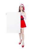 Beautiful sexy woman wearing santa claus clothes with blank sign. Isolated on white background Royalty Free Stock Photo