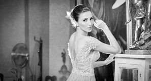 Beautiful sexy woman in white lace dress in vintage scenery. Portrait of brunette young woman with creative hair cut posing in luxury indoor. Attractive young Stock Image