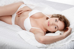 Beautiful sexy woman in white lingerie lying  on her bed. Stock Photography