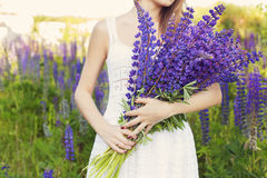 Beautiful sexy woman in white sundress with a bouquet in the hands of lupine in field at sunset Royalty Free Stock Photo