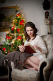 Beautiful sexy woman with Xmas tree in background reading a book sitting on chair. Portrait of a woman reading a book cosy scenery Stock Image