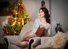 Beautiful sexy woman with Xmas tree in background reading a book sitting on chair. Portrait of a woman reading a book cosy scenery Royalty Free Stock Photos