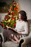 Beautiful sexy woman with Xmas tree in background reading a book sitting on chair. Portrait of a woman reading a book sitting. Comfortable with a blanket on Stock Photo