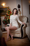 Beautiful sexy woman with Xmas tree in background sitting on elegant chair in cozy scenery. Portrait of girl posing pretty Royalty Free Stock Images
