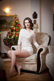 Beautiful sexy woman with Xmas tree in background sitting on elegant chair in cozy scenery. Portrait of girl posing pretty Stock Photography