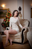 Beautiful sexy woman with Xmas tree in background sitting on elegant chair in cozy scenery. Portrait of girl posing pretty Stock Photo