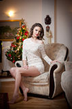 Beautiful woman with Xmas tree in background sitting on elegant chair in cozy scenery. Portrait of girl posing pretty Stock Images