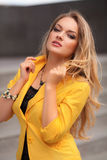 Beautiful woman with yellow jacket and blond hair posing outdoor. Fashion girl Stock Photography