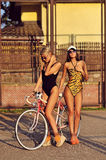 Beautiful women in swimsuits posing near a vintage bike Royalty Free Stock Photography