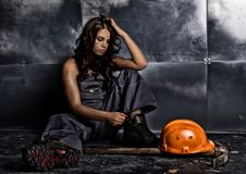 Beautiful tired miner worker sitting on a floor on steel background, pickaxe and orange helmet lies nearby stock photo