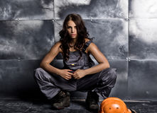 Beautiful sexy worker with a pickaxe and helmet. Seductive and beautiful woman miner sitting on a floor on steel Royalty Free Stock Image