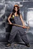 Beautiful sexy worker with a pickaxe. Seductive and beautiful woman miner on a steel background