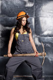 Beautiful worker with a pickaxe. Seductive and beautiful woman miner on a steel background Royalty Free Stock Photo