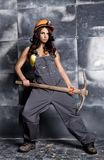 Beautiful worker with a pickaxe. Seductive and beautiful woman miner on a steel background Stock Photos