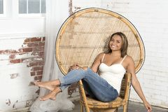 Young woman in white tank and blue jeans relaxes. Beautiful and young biracial woman wearing a white tank top and blue jeans sits in a large wicker chair royalty free stock photo