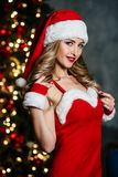 Sexy young blonde woman in red Santa Claus costume with red shoes and white cup of tea coffee smiling Stock Images
