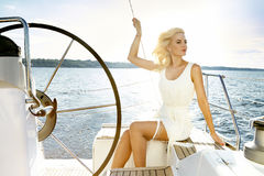 Beautiful young blonde woman, riding a boat on the water, itinerary, beautiful makeup, clothing, summer, sun, perfect body fi Royalty Free Stock Images