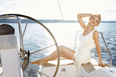 Beautiful sexy young blonde woman, riding a boat on the water, itinerary, beautiful makeup, clothing, summer, sun, perfect body fi Royalty Free Stock Images