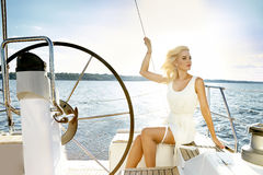 Beautiful young blonde woman, riding a boat on the water, itinerary, beautiful makeup, clothing, summer, sun, perfect body fi Royalty Free Stock Photo