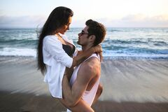 Beautiful, sexy, young caucasian couple cuddling on the beach at sunset time near ocean during summer vacation o