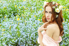 Beautiful young girl with long red hair with flowers in her hair, sitting in a field in blue flowers Stock Image