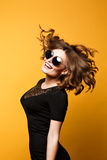 Beautiful young girl with perfect slim figure in large round mirrored sunglasses jumps curly hair scattered Royalty Free Stock Photography