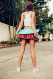 Beautiful sexy young lady in erotic mini skirt with a skateboard Stock Photos