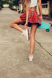 Beautiful sexy young lady in erotic mini skirt with a skateboard Royalty Free Stock Image