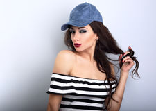 Beautiful young make-up model in blue cap holding long hair Royalty Free Stock Images